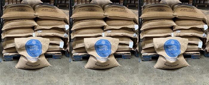 Bags of Swiss Water decaf green coffee stacked on a pallet at the Sweet Maria's warehouse.