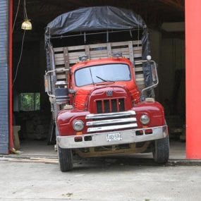 An old flat bed truck is loaded with green coffee at a Colombian coffee warehouse.